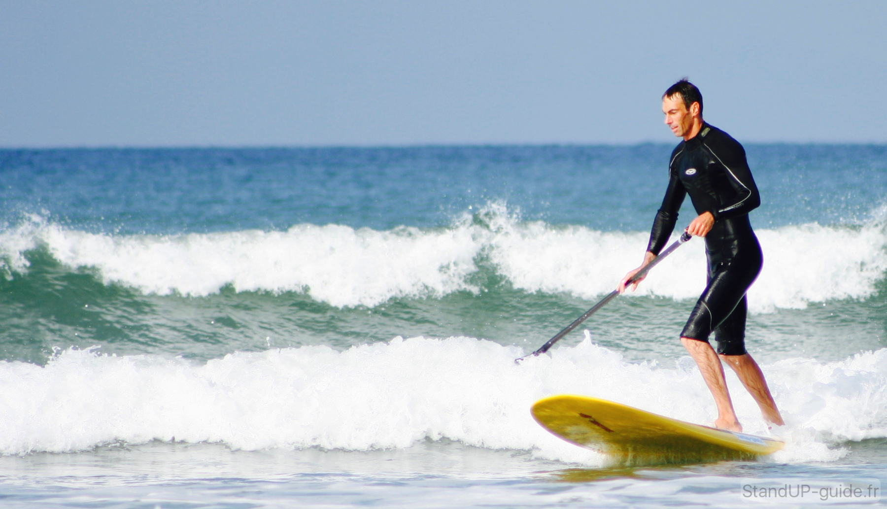 Surfer une vague en paddle